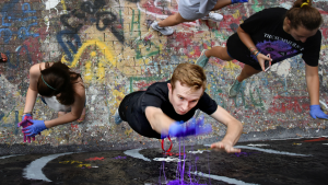 Students using hands to paint wall of free expression tunnel