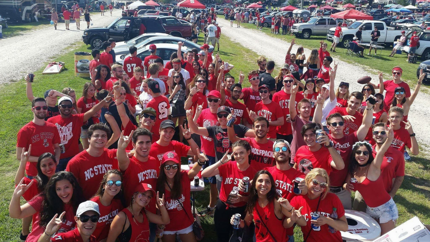 Large group of NC State students in parking lot at a tailgate