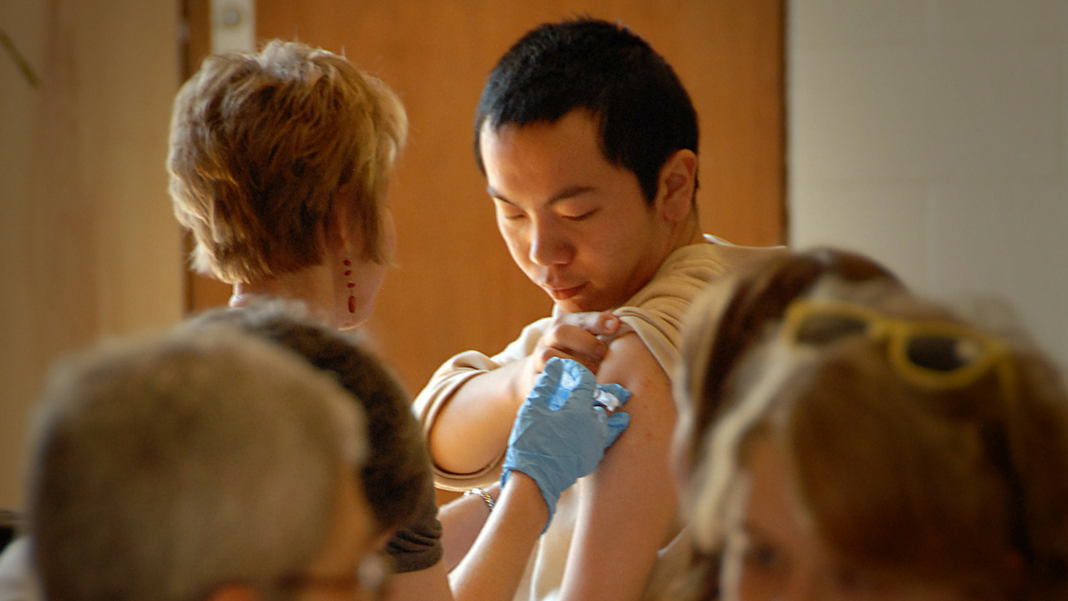 woman wearing gloves injecting vaccination into male international student