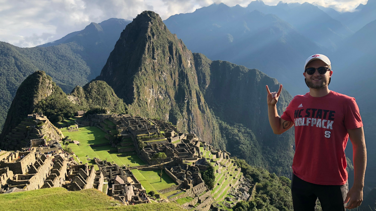 male student wearing NC State shirt with Machu Picchu in background
