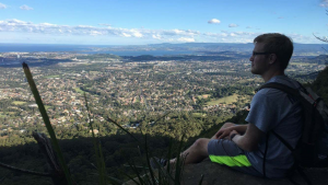 Male sitting on hill overlooking city of Wollongong